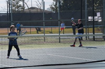 Two youth boys playing tennis on outdoor court